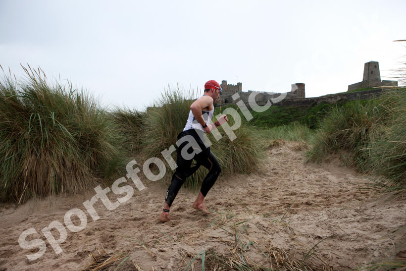 In transition from swimming to cycle during the Bamburgh Triathlon with Bamburgh Castle as a backdrop as the rain starts
